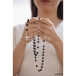Woman praying with rosary beads 64238