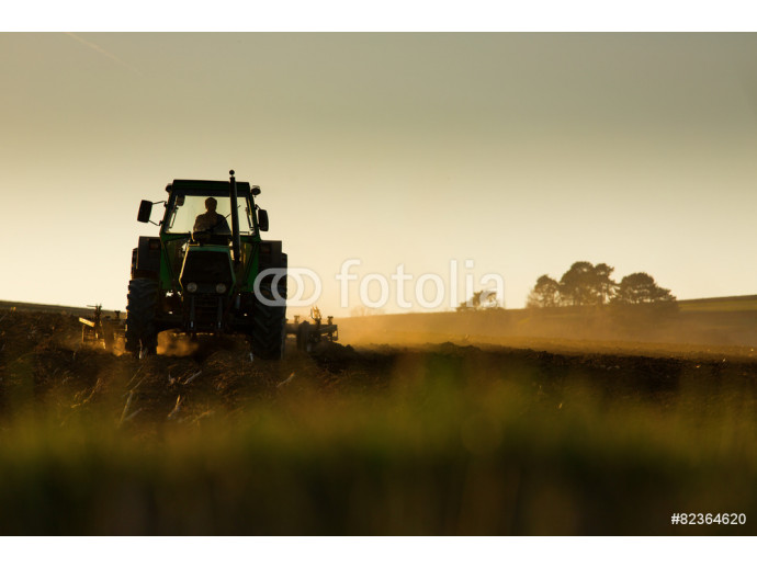 Tractor in sunset plowing the field 64238