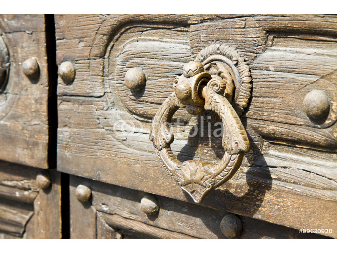 Detail of an old knocker of an old wooden door 64238
