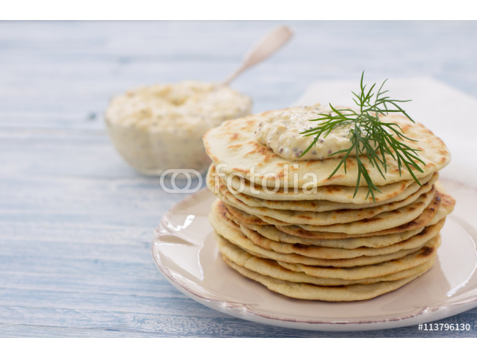 Flat bread with egg dip and dill on a blue wooden background, selective focus 64238