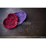 Knitted red and purple hearts on a wood background 64238