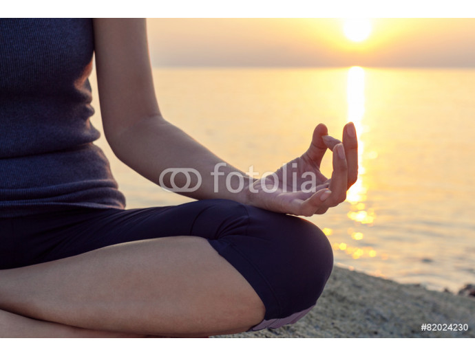 The woman meditating in a yoga pose on the tropical beach. 64238