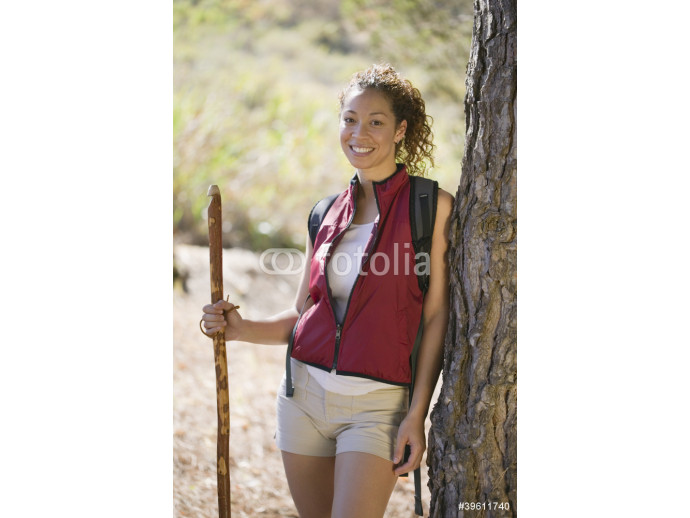 African American female hiker leaning on tree 64238