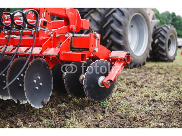 Plow modern tech red tractor close up on an agricultural field Mechanism 64238
