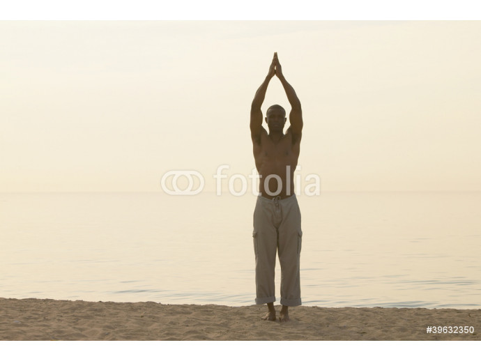African man doing yoga at beach 64238