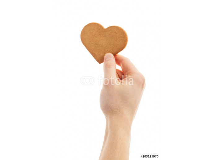 hand is holding a love shaped gingerbread cookie. 64238