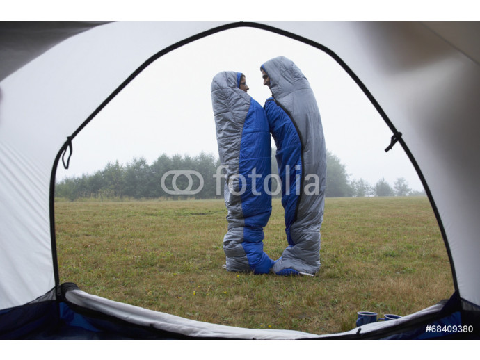 Indian couple wrapped in sleeping bags at campsite 64238