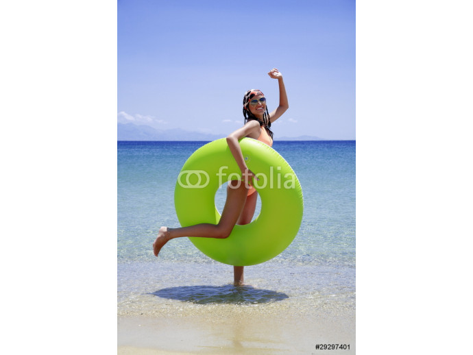 Young woman on beach with inflatable life ring 64238