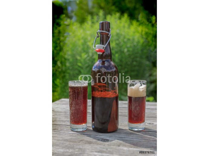 brown glass bottle and two tall glasses full of frothy dark beer on rustic wooden table in summer garden 64238
