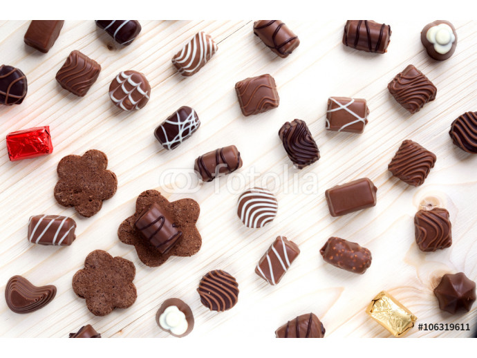 abundance of chocolates on a light wooden background close up, the top view 64238