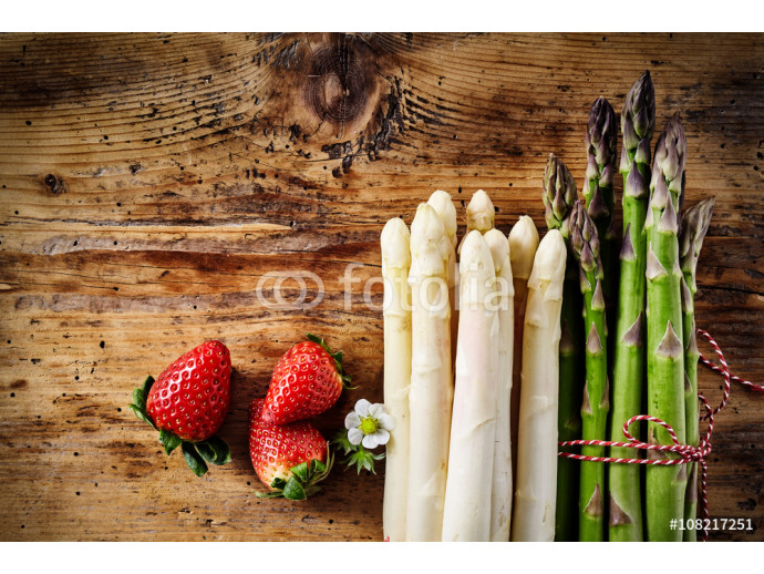 Strawberries and asparagus spears on wooden table 64238