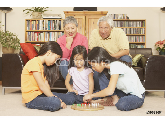 Three young Asian sisters playing chinese checkers while grandparents watch 64238