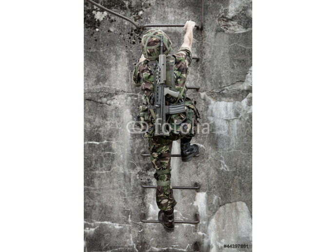 Young soldier with gun climbing 64238