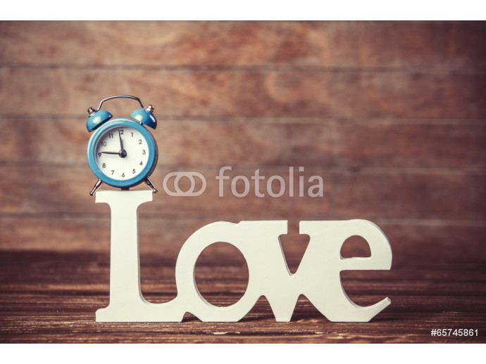 Alarm clock and word Love on wooden table. 64238