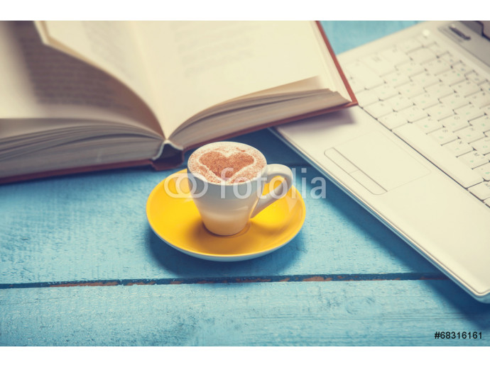 Cup of coffe with laptop and book on blue wooden table. 64238