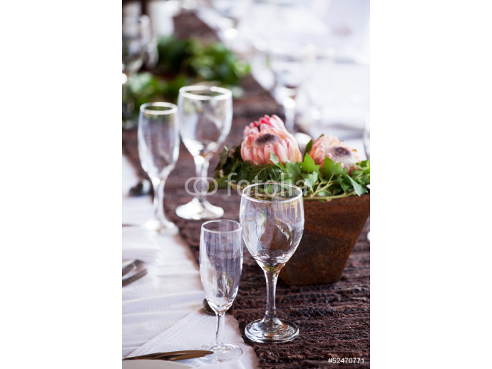 Wine and champagne glasses on a table with protea flowers 64238
