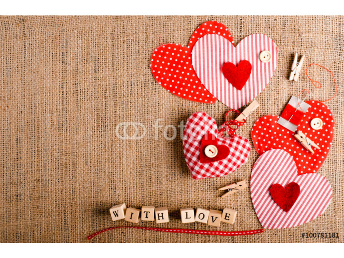 "Sewing set: fabrics, threads, pins, buttons, tape, handmade hearts, words ""with love"" on cubes, burlap, sackcloth background. Retro design effects. 64238"