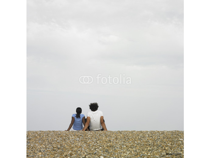 Couple sitting together at beach 64238