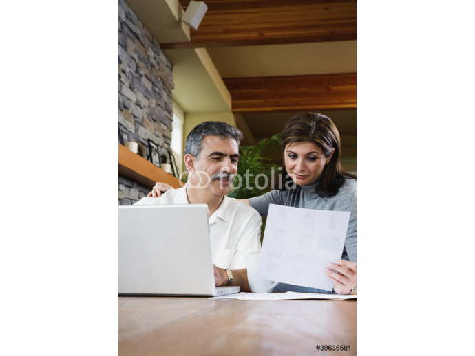 Middle-aged couple looking at paperwork and laptop 64238
