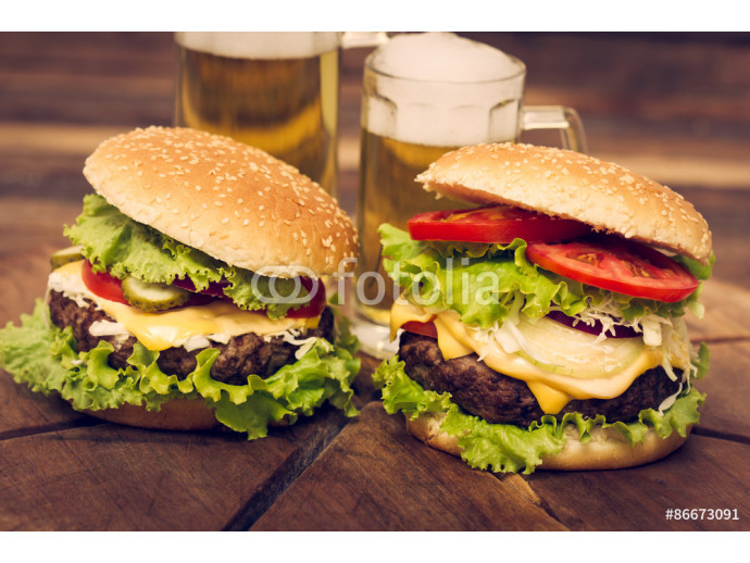 Two hamburgers on the table with beer 64238