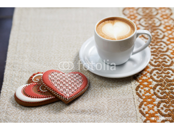 Drinking love. Closeup of heart shaped gingerbread heart shaped cookies served with a cup of cappuccino in sunlight beams 64238