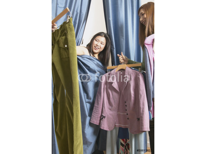 Woman covered with curtain from dressing room looking at clothes 64238