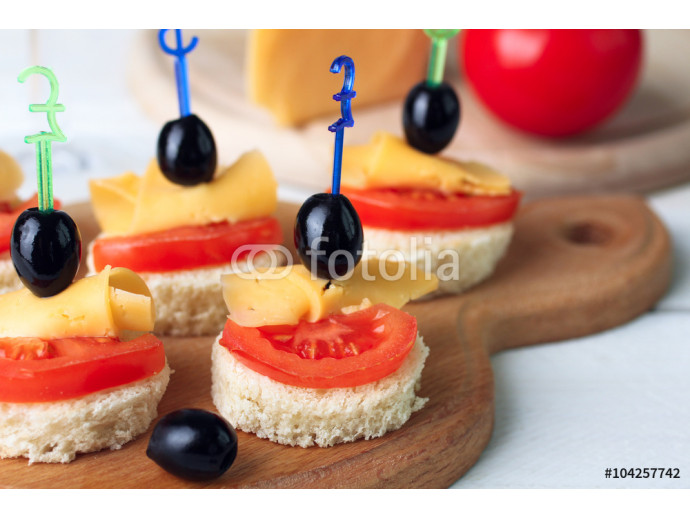 delicious canapes on a wooden cutting Board on white wooden background 64238