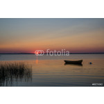 Lone rowboat in calm water at sunset 64238
