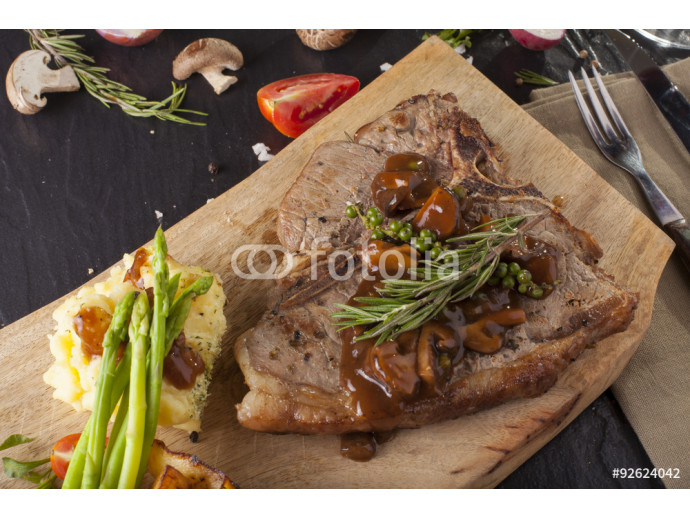 T-bone steak, a prepared piece of grilled T-bone steak brown sauce with mashed potato and vegetable on dining table with red wine decorated 64238