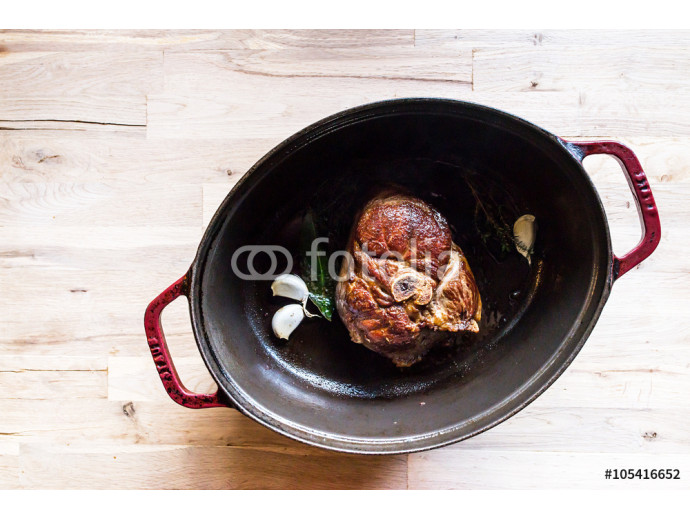 cooking a beautiful grilled slice of an organic leg of lamb meat in a a cooking pot with garlic, thyme and bay laurel 64238