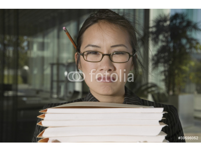 Close up portrait of frustrated businesswoman with stacks of files 64238