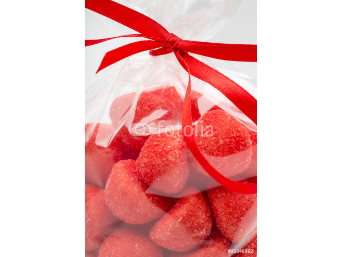 Closeup on luxury bag of candy strawberries with red ribbon 64238