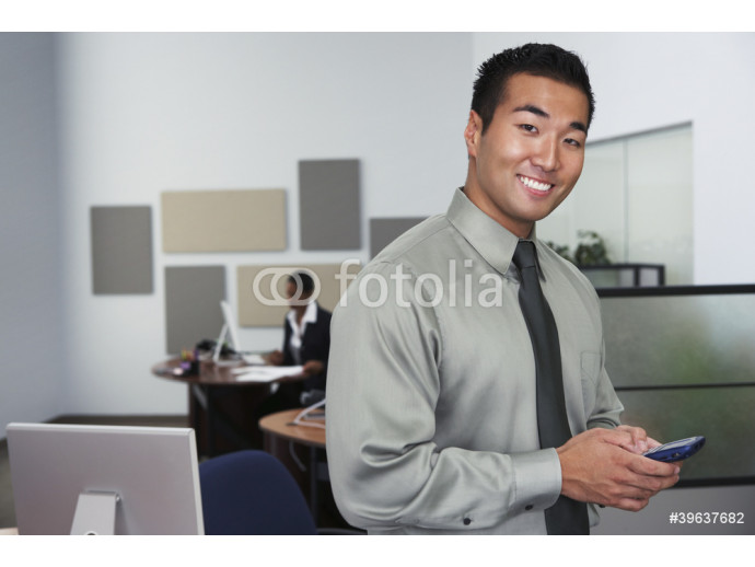 Portrait of Asian businessman holding cell phone 64238