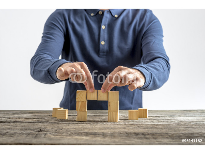 Fototapeta Front view of a man making a bridge with wooden cubes 64238