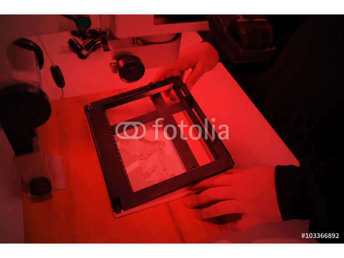 Photographer in the laboratory with  enlarger projects the image from a negative on photo paper 64238