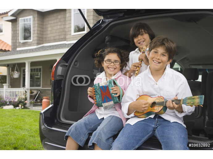 Siblings sitting on tailgate of car playing toy instruments 64238