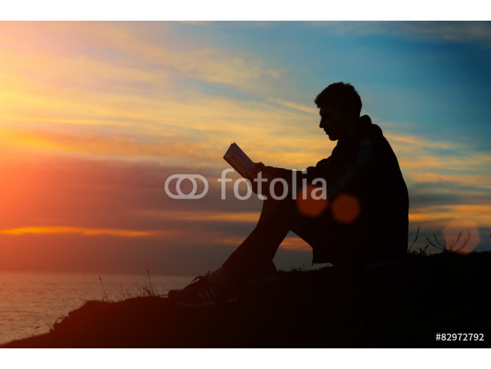 Fototapeta Silhouette of a man sitting on breakwater in evening near sea, r 64238
