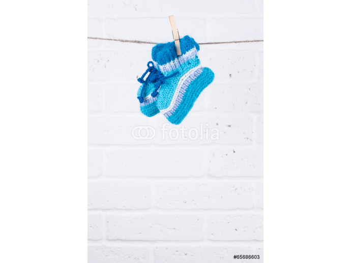 Papier peint moderne knitted baby socks hanging on clothesline against white brick wa 64238