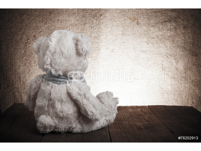 Teddy bear is sitting on the old wooden table. Toned 64238