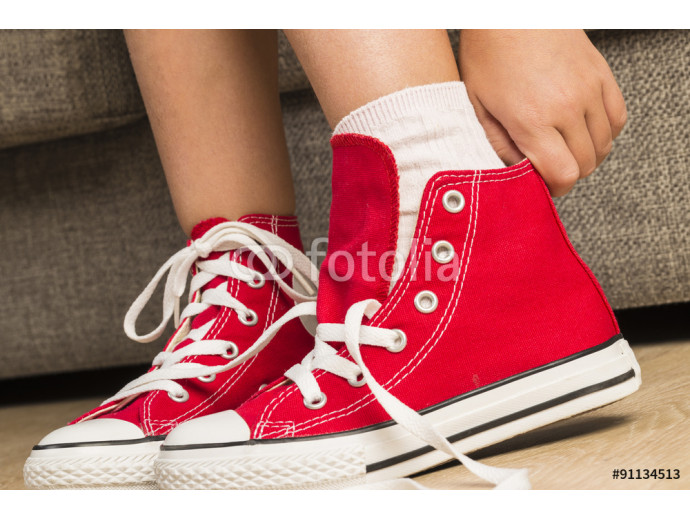 Girl wearing a pair of red sneakers 64238