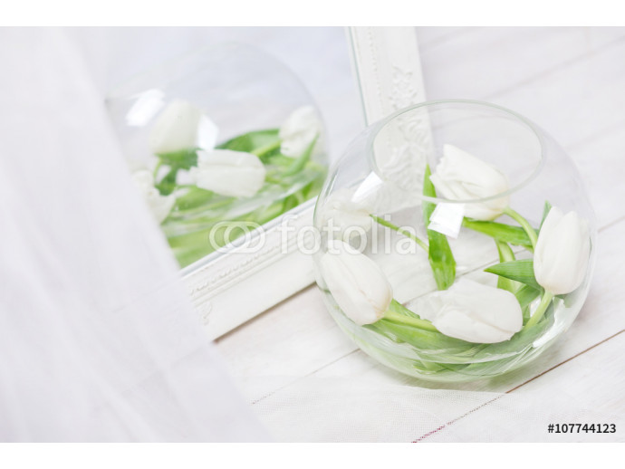 Fresh white tulips in a spherical glass vase. Closeup image 64238