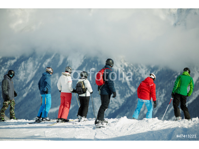 Group of young skiers stands on edge of snowy hillslope 64238