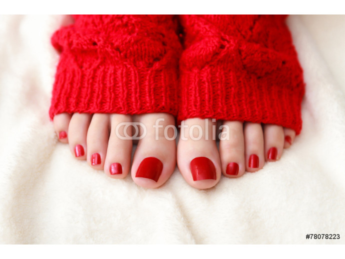 Female feet with a pedicure in red socks 64238