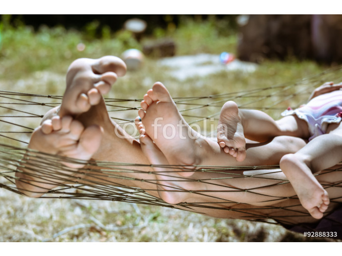 Closeup of happy family lying on hammock barefoot in summer 64238