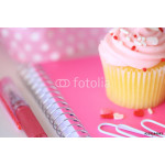 A frosted pink cupcake on a pink notebook with paperclips, a pen, and a ribbon. 64238