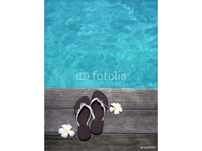 women sandals on a wooden floor with flowers near the water 64238