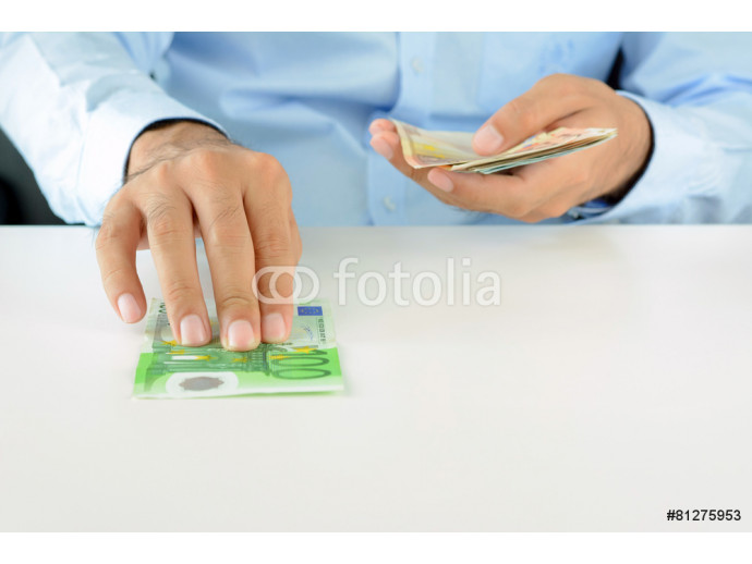 Hand giving (pushing) money, Euro currency (EUR), on white desk 64238