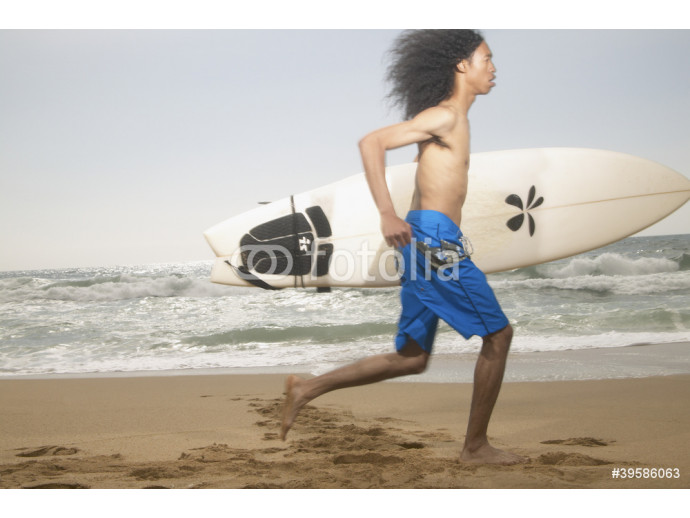 Young man running along beach with surfboard 64238