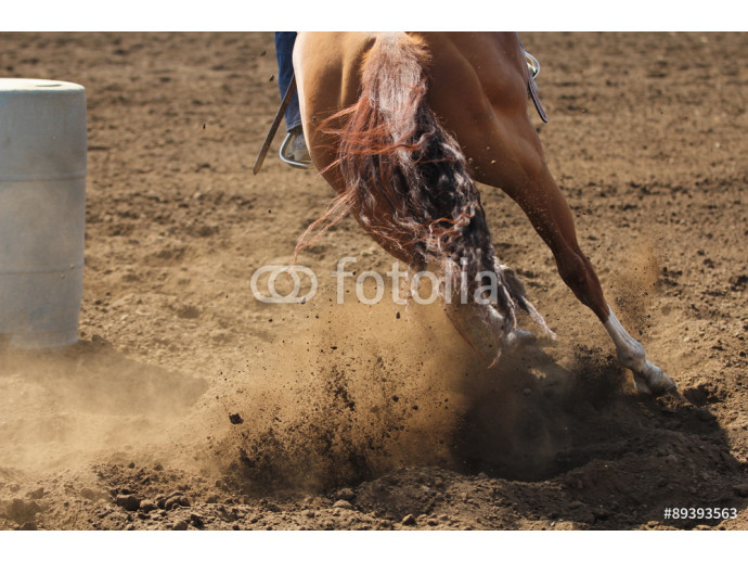 A barrel racing horse is sliding and kicking up dirt while galloping around a barrel. 64238