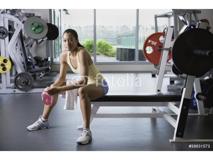 Woman sitting in weight bench at gym 64238